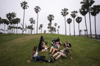 FILE - In this May 5, 2021, file photo, a group of friends, who said they are fully vaccinated for COVID-19, mingle on the beach in the Venice section of Los Angeles. COVID-19 deaths in the U.S. have tumbled to an average of just over 600 per day — the lowest level in 10 months — with the number of lives lost dropping to single digits in well over half the states and hitting zero on some days. (AP Photo/Jae C. Hong, File)