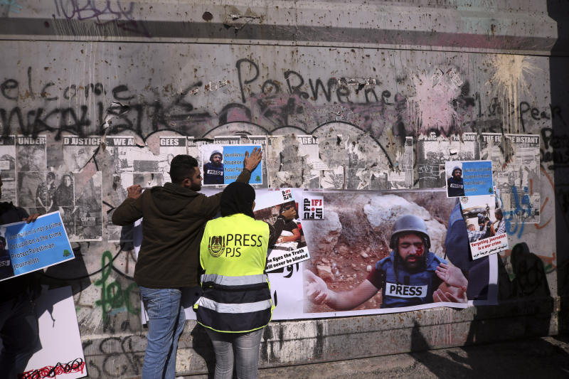 Palestinian journalist hang posters on a separation barrier in Bethlehem, West Bank, Sunday, Nov. 18, 2019, during a protest in support of a 35 year-old photographer Muath Amarneh. Amarneh's relatives say he has lost vision in one eye after apparently being struck by Israeli fire while covering a demonstration in the West Bank. Israel's paramilitary border police unit says it did not target him. (AP Photo/Mahmoud Illean)