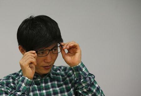 Shin Dong-hyuk adjusts his glasses during an interview with Reuters in Seoul