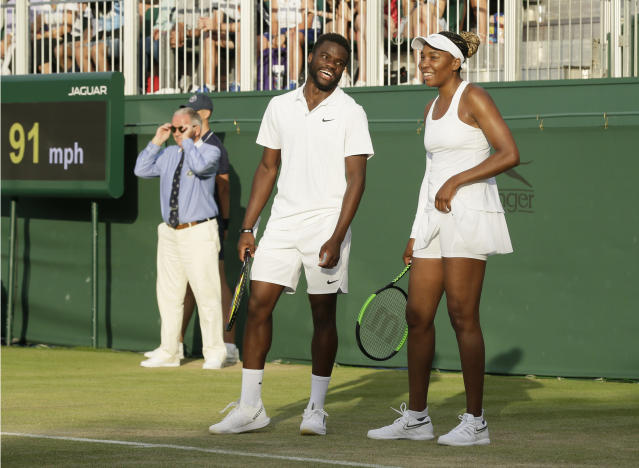 United States's Frances Tiafoe, left, and Venus Williams laugh during their Mixed Doubles match during day five of the Wimbledon Tennis Championships in London, Friday, July 5, 2019. (AP Photo/Tim Ireland)