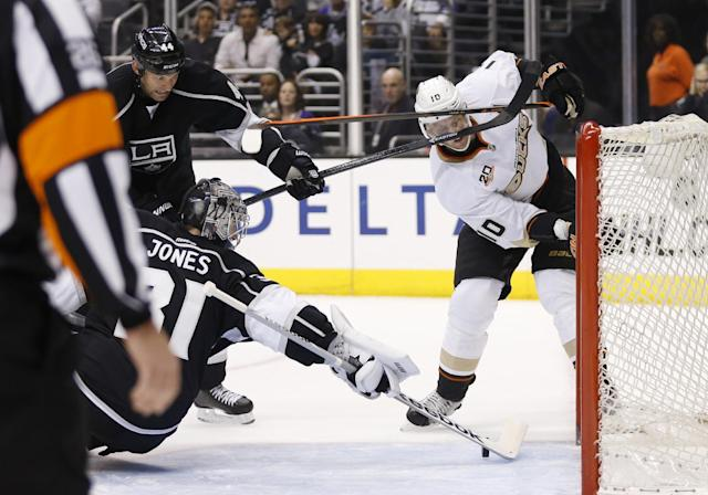Anaheim Ducks right wing Corey Perry, right, takes a high stick to the face from Los Angeles Kings defenseman Robyn Regehr, left, as Los Angeles Kings goalie Martin Jones makes a save during the first period of an NHL hockey game in Los Angeles, Saturday, March 15, 2014. (AP Photo/Danny Moloshok)
