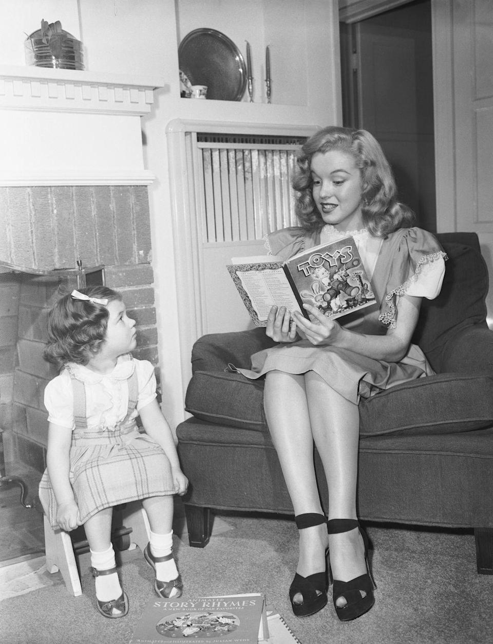 <p>The <em>Some Like it Hot</em> star reads a children's book to the young daughter of a fellow Hollywood studio player.</p>