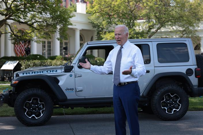President Joe Biden answers questions from reporters after driving a Jeep Wrangler Rubicon Xe around the White House driveway following remarks during an event on the South Lawn of the White House 5 August 2021. (Getty Images)