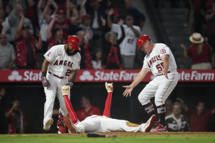Los Angeles Angels designated hitter Shohei Ohtani, center, celebrates with Luis Rengifo (2) and third base coach Brian Butterfield (55) after sliding in to home to score during the ninth inning of a baseball game against the Baltimore Orioles Friday, July 2, 2021, in Anaheim, Calif. The run won the game for the Angels 8-7. (AP Photo/Ashley Landis)