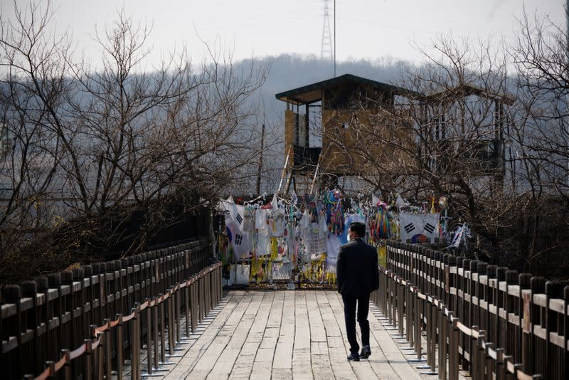 A man walks in front of a military fence near the demilitarized zone separating the two Koreas in Paju