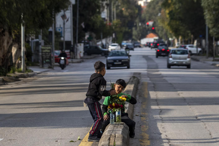 Syrian refugee children sell flowers at a traffic light in Beirut, Lebanon, Saturday, April 3, 2021. Lebanese authorities imposed a three-day nationwide curfew as of Saturday morning to try limit the spread of the virus during the Easter holidays. (AP Photo/Hassan Ammar)