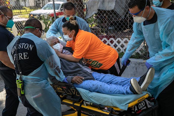 A woman embraces her husband with possible Covid-9 symptoms before medics transported him to a hospital on Aug. 13, 2020, in Houston.