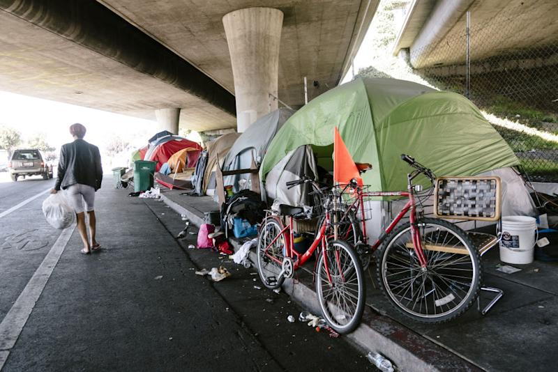 A person walks past a homeless encampment in Oakland, California, on Friday, Aug. 30, 2019. | A person walks past a homeless encampment in Oakland, California, on Friday, Aug. 30, 2019.