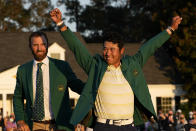FILE - In this Sunday, April 11, 2021 file photo, Hideki Matsuyama, of Japan, puts on the champion's green jacket after winning the Masters golf tournament as Dustin Johnson watches in Augusta, Ga. Matsuyama already is thinking about what to serve at the champions dinner next April. It likely will include sushi. (AP Photo/David J. Phillip, File)