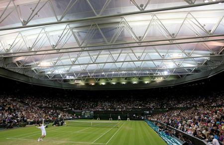 FILE PHOTO: Andy Murray of Britain (FOREGROUND) serves to Ivan Ljubicic of Croatia under the closed roof on Centre Court at the Wimbledon tennis championships in London, Britain, June 24, 2011.         REUTERS/Stefan Wermuth/File Photo