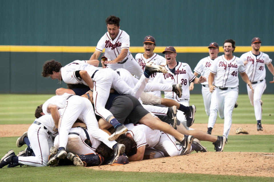 Virginia's Drew Hamrock, top, leaps on top of a dogpile with teammates after an NCAA college baseball tournament super regional game against Dallas Baptist, Monday, June 14, 2021, in Columbia, S.C. (AP Photo/Sean Rayford)