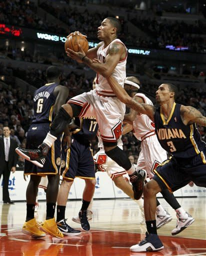 Chicago Bulls point guard Derrick Rose, center, drives and scores past Indiana Pacers shooting guard George Hill, right, during the first half of an NBA basketball game on Wednesday, Jan. 25, 2012, in Chicago. (AP Photo/Charles Rex Arbogast)