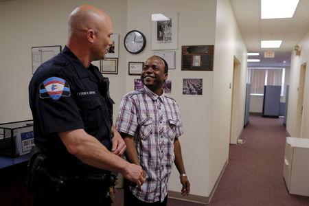 Lewiston Police Officer Patrick Griffin (L), a community resource officer, talks to Jama Mohamed, literacy and volunteering director at Maine Immigrant and Refugee Services facility, in Lewiston, Maine June 1, 2015. REUTERS/Brian Snyder