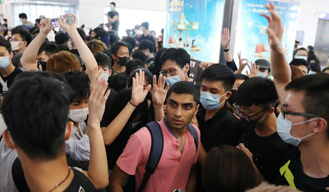Travellers attempt to navigate through a crowd of anti-government protesters at Hong Kong International Airport on Tuesday. Photo: Sam Tsang