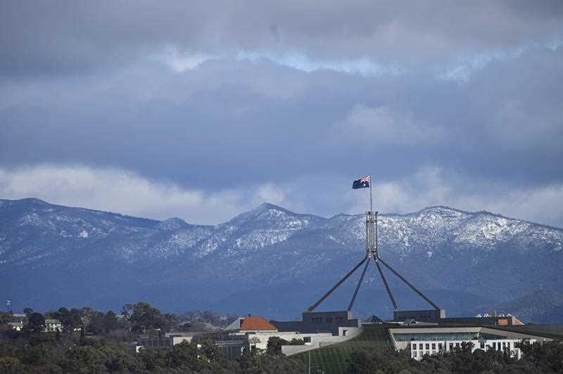 Parliament House is seen in front of snow-covered hills surrounding the Australian Capital Territory (ACT) in Canberra in August, 2019.