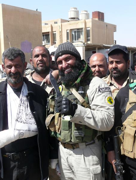 Ayyub Faleh al-Rubaie (centre), known as Abu Azrael -- Father of the Angel of Death -- poses with Shiite fighters at the Speicher military base, near the northern Iraqi city of Tikrit, on March 14, 2015 (AFP Photo/W.G. Dunlop)