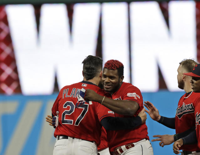 Cleveland Indians' Yasiel Puig, right, is hugged by Kevin Plawecki after Puig hit a game-winning RBI-single in the tenth inning in a baseball game against the Detroit Tigers, Wednesday, Sept. 18, 2019, in Cleveland. The Indians won 2-1 in ten innings. (AP Photo/Tony Dejak)