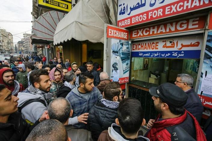 Lebanese anti-government protesters gather at the entrance of a currency exchange bureau in the northern port city of Tripoli (AFP Photo/Ibrahim CHALHOUB)