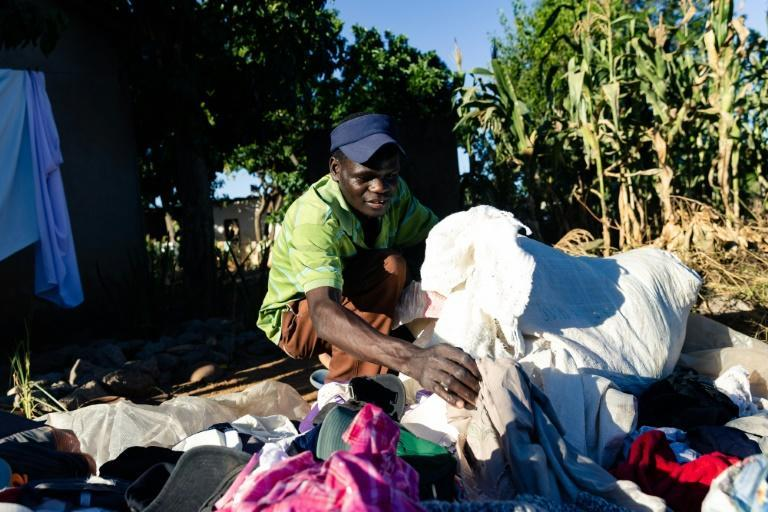 Kenneth Tauro sorts through a sack full of second-hand clothing as he prepares to head out to market in Epworth township in Harare