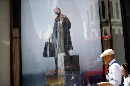 FILE PHOTO: An advertisement containing a jacket with Burberry logo pattern is pictured at a window of a Burberry store in central London