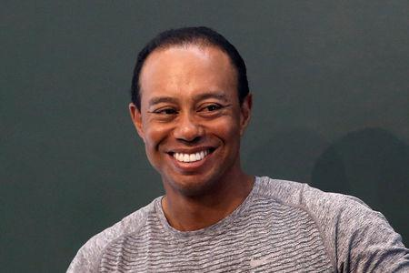 "Golfer Tiger Woods smiles as he sits down to sign copies of his new book ""The 1997 Masters: My Story"" at a book signing event at a Barnes & Noble store in New York City, New York, U.S., March 20, 2017. REUTERS/Mike Segar"