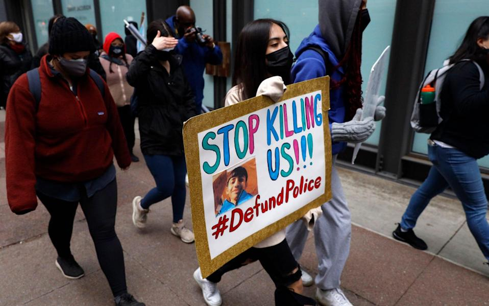"""A protester holding a sign reading """"Stop Killing Us"""" navigates along Chicago's Loop during a peaceful protest on Wednesday - AP"""