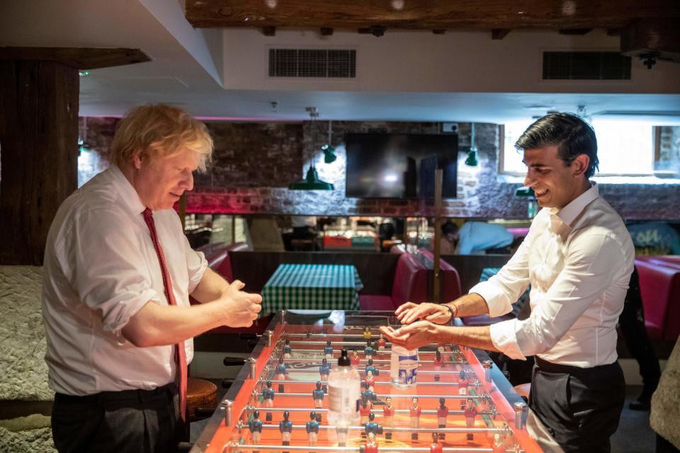 Britain's Prime Minister Boris Johnson (L) and Britain's Chancellor of the Exchequer Rishi Sunak use hand sanitizer on either side of a table football game as they visit Pizza Pilgrims in West India Quay, London Docklands on June 26, 2020 as the restaurant prepares to reopen on July 4 as coronavirus lockdown rules are eased. - The British government on Thursday unveiled plans to get the public out of indoor confinement and on to the streets to boost the economy after three months of coronavirus lockdown. Prime Minister Boris Johnson wants pubs and restaurants to be buzzing in the curtailed summer season, despite continued social distancing rules and restrictions. (Photo by Heathcliff O'Malley / POOL / AFP) (Photo by HEATHCLIFF O'MALLEY/POOL/AFP via Getty Images)