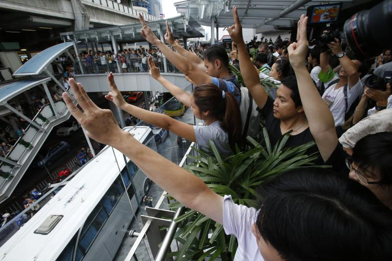 Protesters against military rule gesture by holding up their three middle fingers in the air, during a brief demonstration at a shopping mall in Bangkok