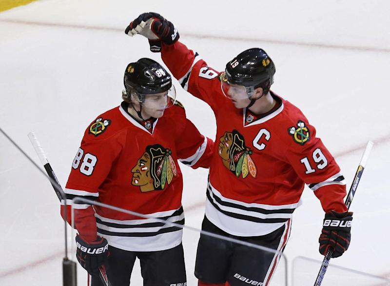 Chicago Blackhawks center Jonathan Toews (19) celebrates his goal with Patrick Kane during the third period of an NHL hockey game against the Columbus Blue Jackets on Thursday, March 6, 2014, in Chicago. The Blackhawks won 6-1. (AP Photo/Charles Rex Arbogast)