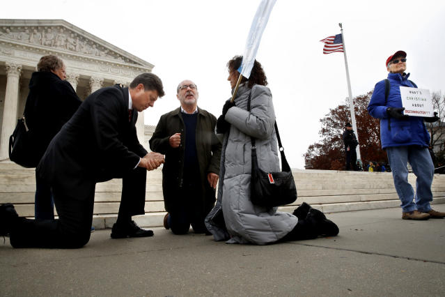 "<p>Rev. Brad Wells, left, Rev. Patrick Mahoney, and Paula Oas, kneel in prayer in front of the Supreme Court, as a counter-protester holds a sign that says ""What's Christian About Discrimination,"" while the court hears the 'Masterpiece Cakeshop v. Colorado Civil Rights Commission' case, Tuesday, Dec. 5, 2017, in Washington. (Photo: Jacquelyn Martin/AP) </p>"