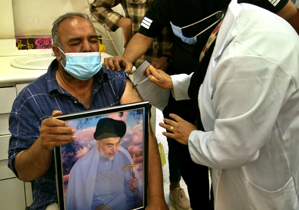 A follower of populist Shiite cleric Muqtada al-Sadr holds a picture of him while receiving a dose of the Chinese Sinopharm coronavirus vaccine at a clinic in Sadr City, Baghdad, Iraq, Wednesday, May 4, 2021. Iraq's vaccine rollout had been faltering for weeks. Apathy, fear and rumors kept many from getting vaccinated despite a serious surge in coronavirus infections and calls by the government for people to register for shots. It took al-Sadr's public endorsement of vaccinations — and images of him getting the shot — to turn things around. (AP Photo/Hadi Mizban)