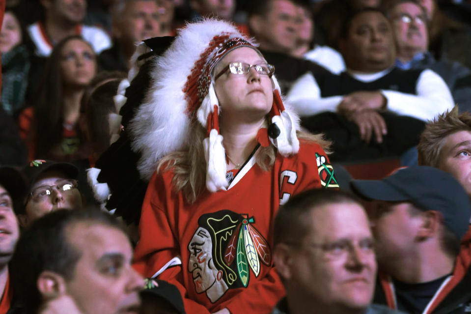 FILE - In this Feb. 19, 2013, file photo, Chicago Blackhawks fan Joy Bereckis watches a Blackhawk video before an NHL hockey game between the Blackhawks and the Vancouver Canucks in Chicago. The team announced Wednesday, July 29, 2020, that they are banning headdresses at home games as part of their pledge to honor the Native American community. (AP Photo/Charles Rex Arbogast, File)
