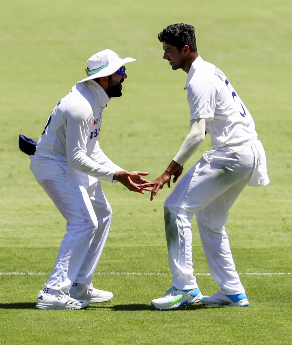 India's Rohit Sharma, left, and teammate Washington Sundar celebrate the dismissal of Australia's Steve Smith during play on the first day of the fourth cricket test between India and Australia at the Gabba, Brisbane, Australia, Friday, Jan. 15, 2021. (AP Photo/Tertius Pickard)