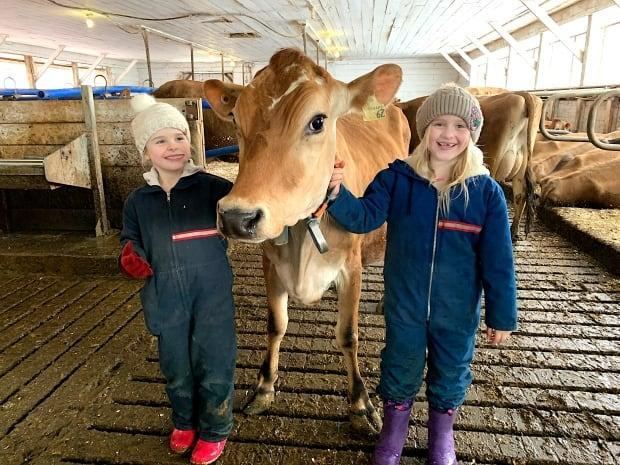 Heidi and Sophie Brosens are shown with Temperance the Jersey cow.