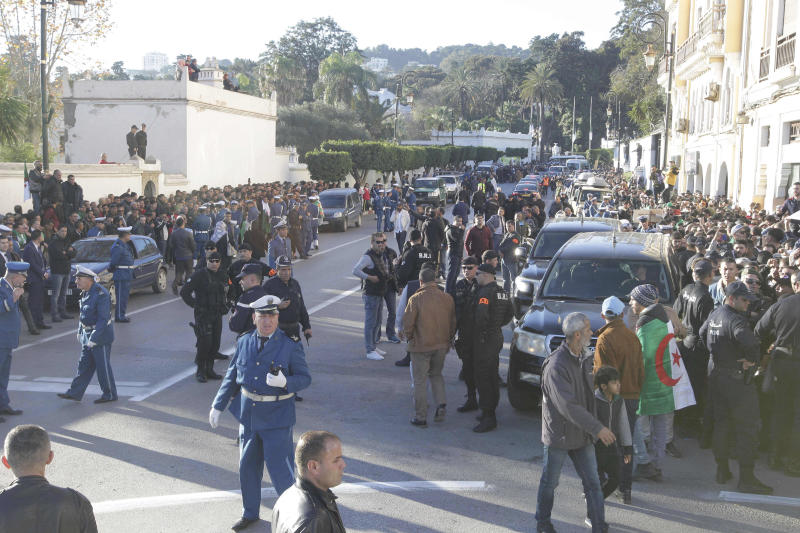People gather during the funeral of late Algerian military chief Gaid Saleh in Algiers, Algeria, Wednesday, Dec. 25, 2019. Algeria is holding an elaborate military funeral for the general who was the de facto ruler of the gas-rich country amid political turmoil throughout this year. (AP Photo/Fateh Guidoum)