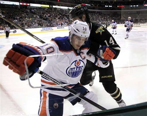 Edmonton Oilers center Shawn Horcoff (10), of Canada, is hit into the glass by Dallas Stars left wing Jamie Benn (14), of Canada, as they battle for a loose puck during the first period of a NHL hockey game on Saturday, Jan. 7, 2012, in Dallas. (AP Photo/John F. Rhodes)