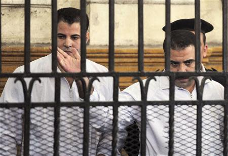 Egyptian policemen Awad Suleiman and Mahmoud Salah react in dock during trial in court in Alexandria