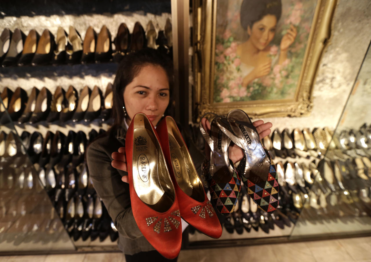 "Jane Ballesteros, the curator of Marikina Museum where more than seven hundred pairs of shoes of former Philippine First Lady Imelda Marcos are housed, holds a pair of Marcos' shoes on Tuesday Sept. 25, 2012 at Marikina city east of Manila, Philippines. At the National Museum in Manila, termites, storms and government neglect have damaged hundreds of pieces of the late strongman Ferdinand Marcos' ""barongs"" as well as that of flamboyant Imelda Marcos' legendary stash of shoes, expensive gowns, and other vanity possessions which were left to oblivion after she and dictator husband were driven to U.S. exile by a 1986 popular revolt. (AP Photo/Bullit Marquez)"