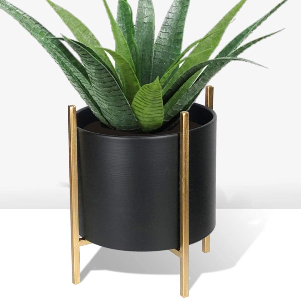 <p>If you have a modern or glam aesthetic, you'll love this <span>Small Mid Century Style Metal Indoor Planter</span> ($29). Flip the gold stand one way for a short placement and the other way for a taller placement.</p>