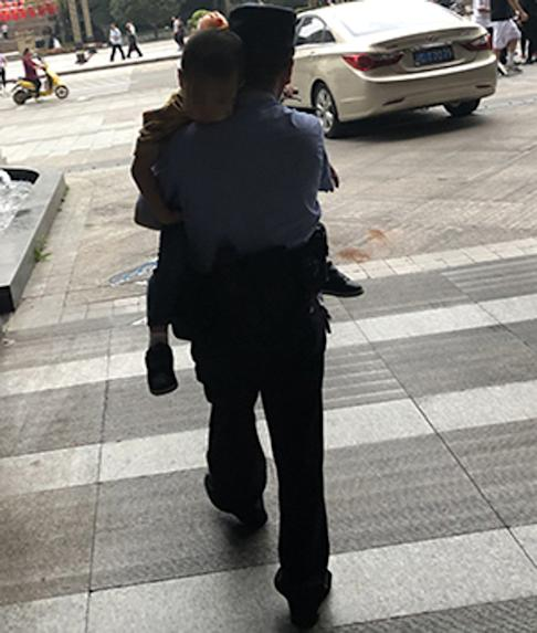 An officer from Chongqing police carries the sleepy four-year-old boy to Dazhu district station and an eventual reunion with his father. Photo: Weibo