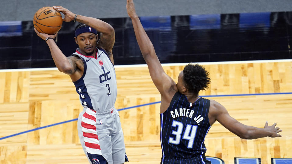 Washington Wizards guard Bradley Beal (3) passes the ball as he is defended by Orlando Magic center Wendell Carter Jr. (34) during the first half of an NBA basketball game Wednesday, April 7, 2021, in Orlando, Fla. (AP Photo/John Raoux)