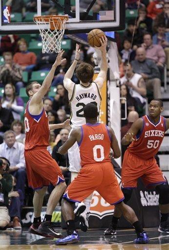 Utah Jazz's Gordon Hayward (20) shoots as Philadelphia 76ers' Spencer Hawes, left, and teammates Jeremy Pargo (0) and Lavoy Allen (50) look on in the first quarter during an NBA basketball game Monday, March 25, 2013, in Salt Lake City. (AP Photo/Rick Bowmer)