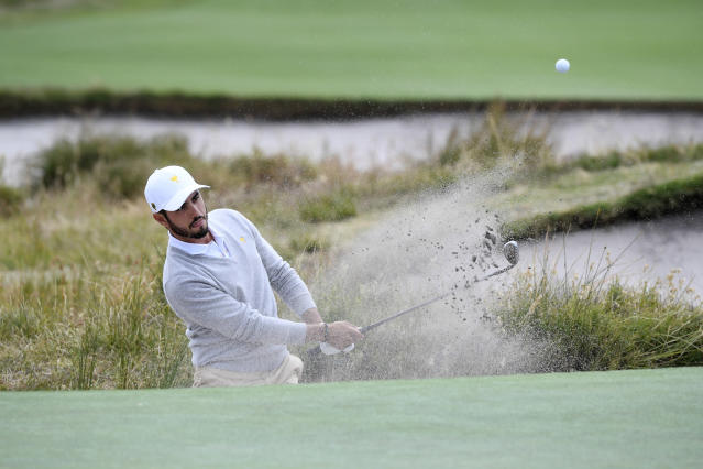 International's Abraham Ancer of Mexico hits out of a bunker during a practice session ahead of the President's Cup Golf tournament in Melbourne, Tuesday, Dec. 10, 2019. (AP Photo/Andy Brownbill)