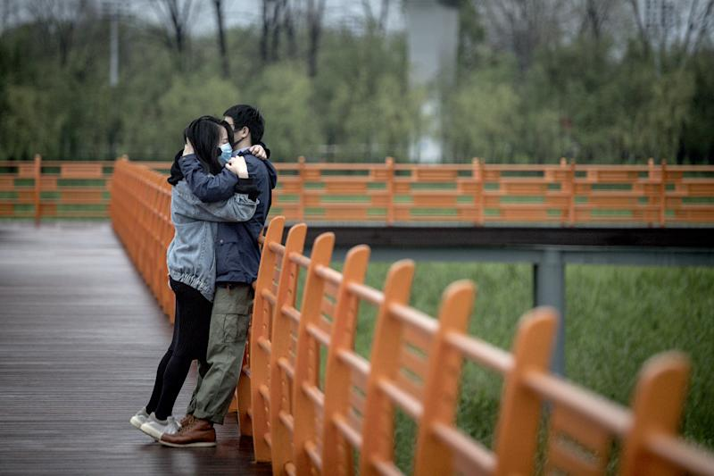 Image: A couple hug in Wuhan (Getty Images)