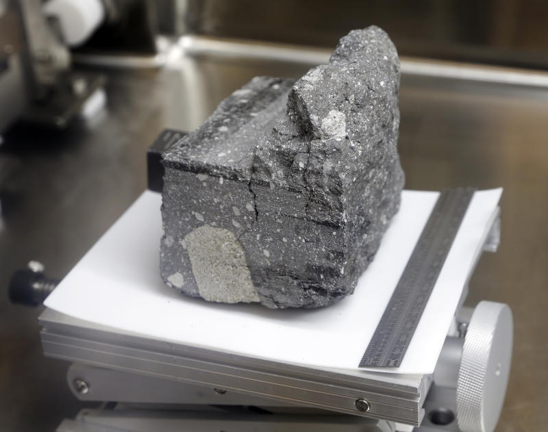 A regolith breccia rock of sintered lunar soil, dating 3.2 billion years old and collected by Apollo 15, is displayed in a pressurized nitrogen-filled case inside the lunar lab at the NASA Johnson Space Center Monday, June 17, 2019, in Houston. (Photo: Michael Wyke/AP)