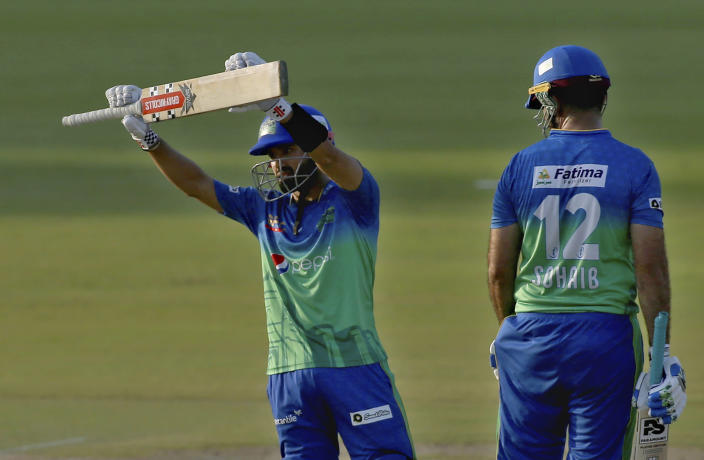 Multan Sultans' Mohammad Rizwan, left, raises bat to celebrate after scoring fifty while teammate Sohaib Maqsood watches during a Pakistan Super League T20 cricket match between Lahore Qalandars and Multan Sultans at the National Stadium, in Karachi, Pakistan, Friday, Feb. 26, 2021. (AP Photo/Fareed Khan)