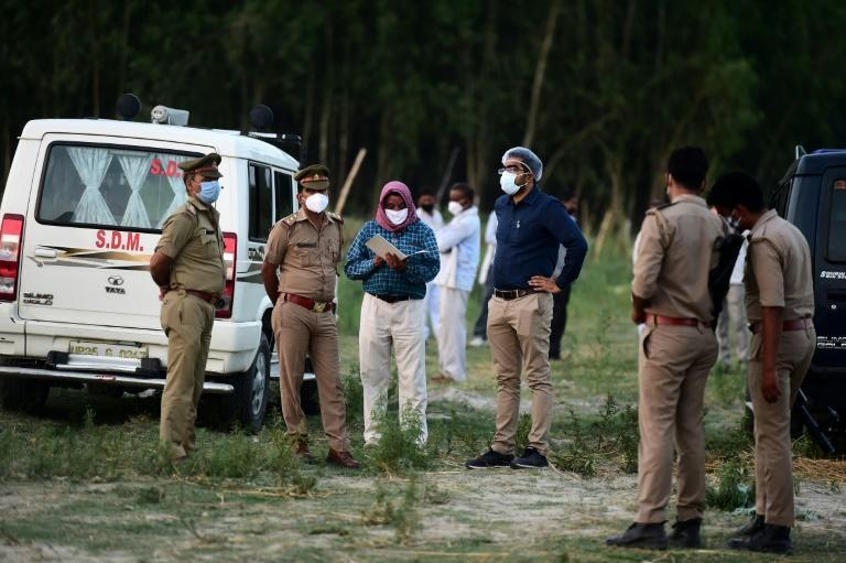 Police and administrative officials inspect a cremation ground on the banks of the Ganges River as the death toll mounts from Covid in India