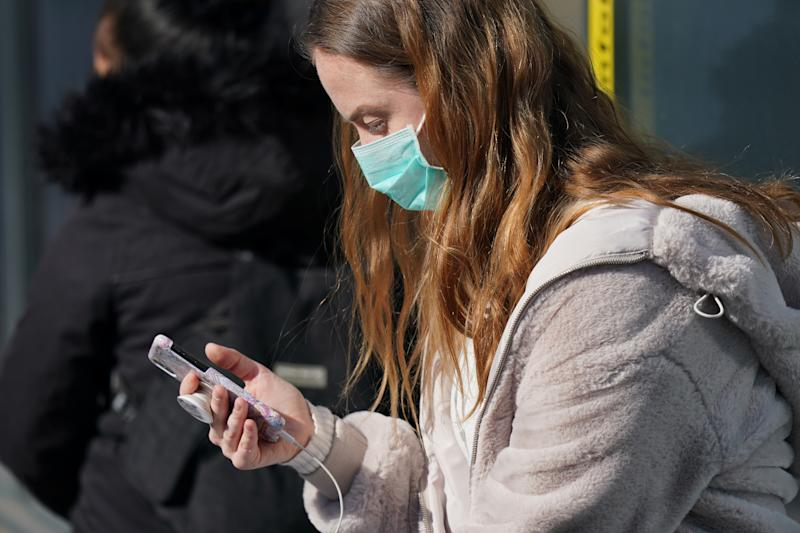 BERLIN, GERMANY - APRIL 27: A young woman wearing a face mask, who said she did not mind being photographed, looks at a smartphone as she waits at a tram at Alexanderplatz on the first day of a nationwide policy to wear protective face masks in stores and while riding public transportation during the novel coronavirus crisis on April 27, 2020 in Berlin, Germany. The German government is introducing steps to ease lockdown restrictions in order to help economic activity to resume while at the same time seeking to prevent a renewed surge in Covid-19 infections. (Photo by Sean Gallup/Getty Images,)