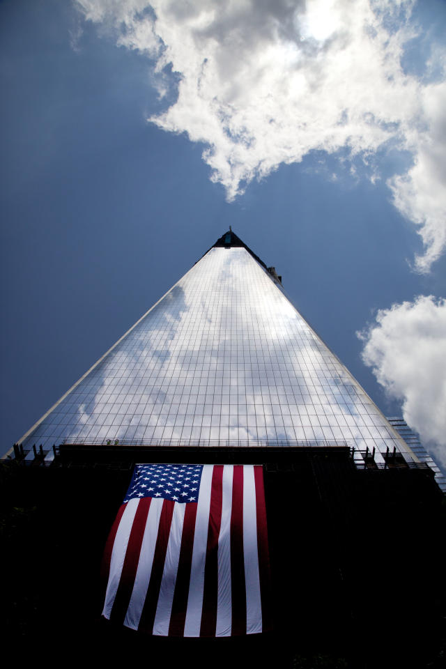 "FILE - In this Thursday, June 14, 2012 file photo, an American flag hangs draped on the side of One World Trade Center, in New York. More than a decade after 9/11, no one's quite sure what to call the spot that was once a smoldering graveyard but is now the site of the fast-rising, 1,776-foot skyscraper that will replace the twin towers. Some are calling the new skyscraper ""One World Trade Center,"" but it's still ""ground zero"" to others. (AP Photo/Mark Lennihan, File)"