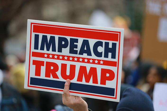 """A man holds up an Impeach """"Trump"""" sign during the Women's Unity Rally hosted by a chapter of Women's March National on Jan. 19, 2019 at Foley Square in New York City. (Photo: Gordon Donovan/Yahoo News)"""
